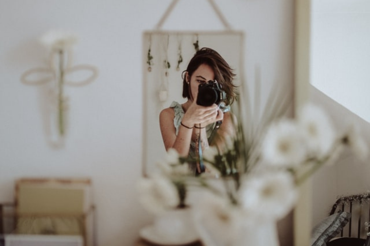 woman holding a camera capturing herself in front of the mirror