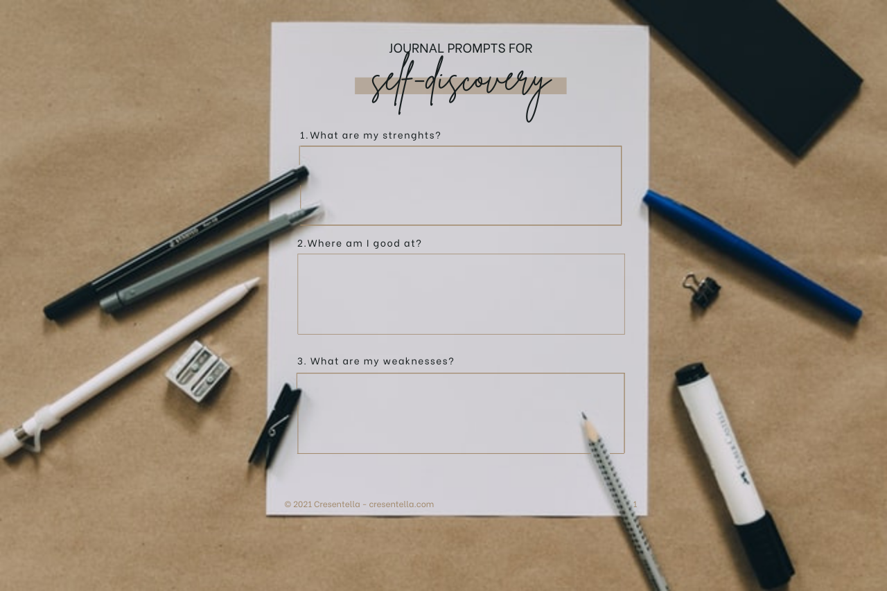 a printed copy of journal prompts for self-discovery in the table along with pen, markers, and paper clips